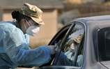 Service member performs COVID-19 test on patient from car