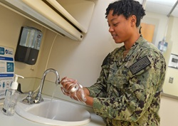 service member washing hands
