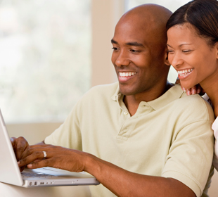 Couple logging onto laptop for secure services